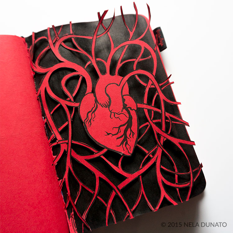Paper-cut anatomic heart in a red sketchbook