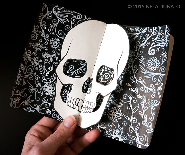 Paper-cut skull over a page of ornament doodles in a sketchbook
