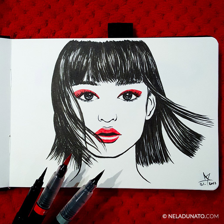 Female portrait with brush pens in a sketchbook